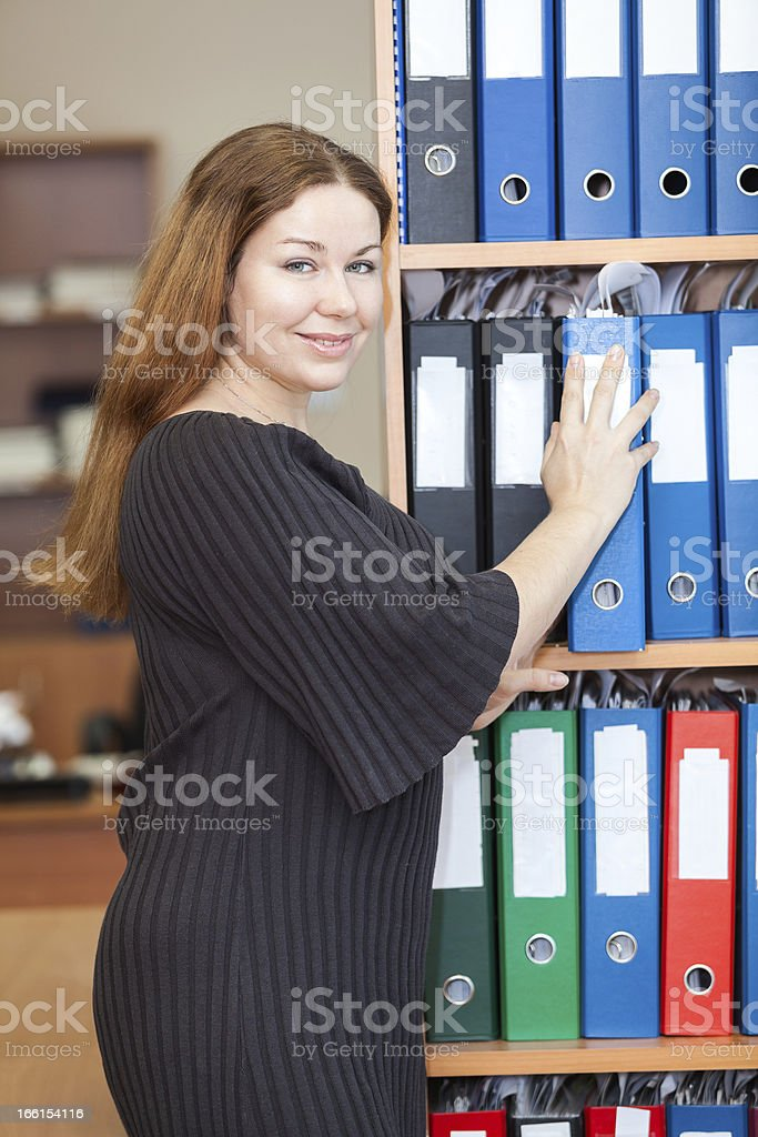 Employee of the office standing next to cabinet with documents royalty-free stock photo