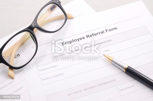 Employee Referral Form With A Pen And Glasses On A Desk Stock