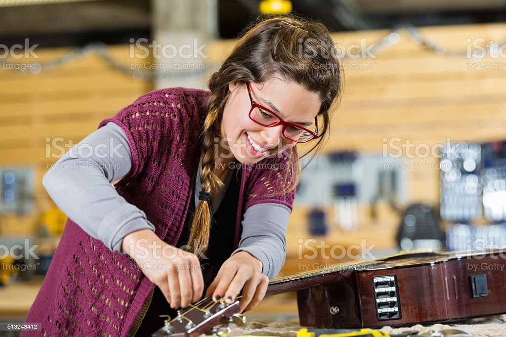 Employee repairing instruments in local guitar shop stock photo