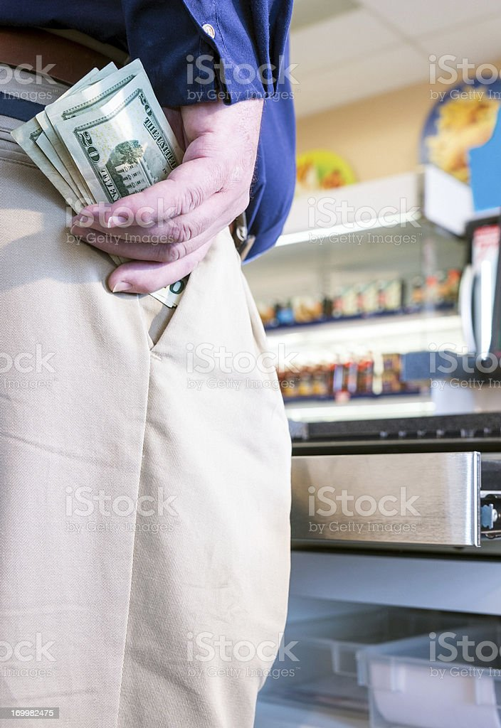 Employee stealing cash from a store register stock photo