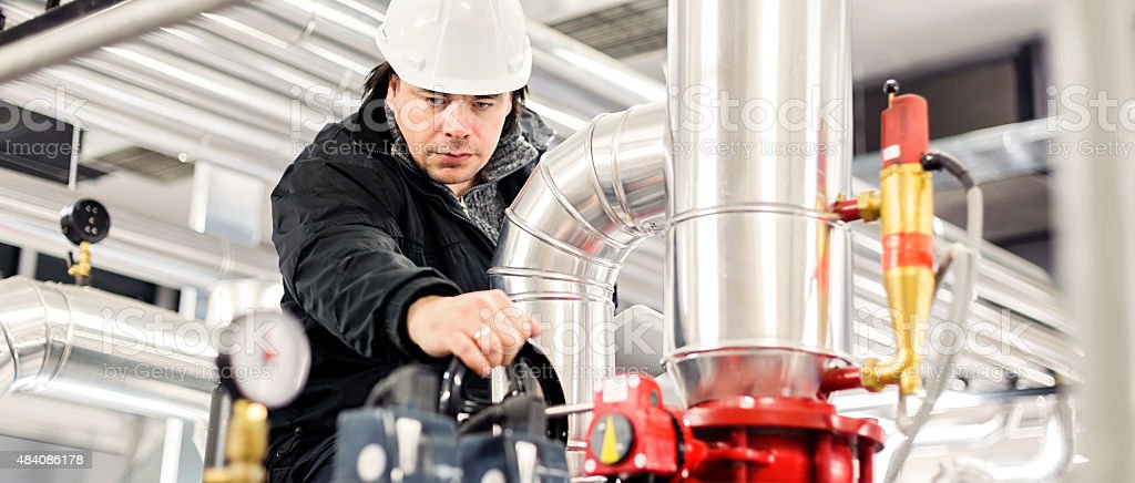 Employee take note in boiler room stock photo