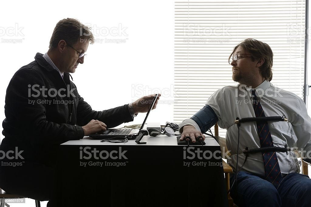 Employee tries to peer at polygraph test screen stock photo