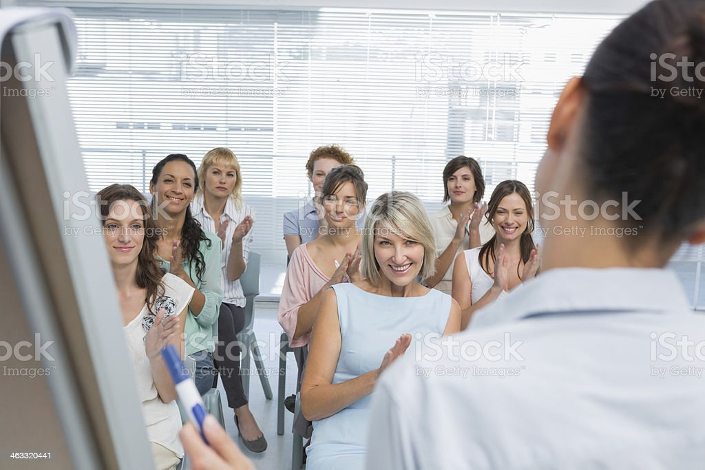 Employees applauding their colleagues presentation stock photo