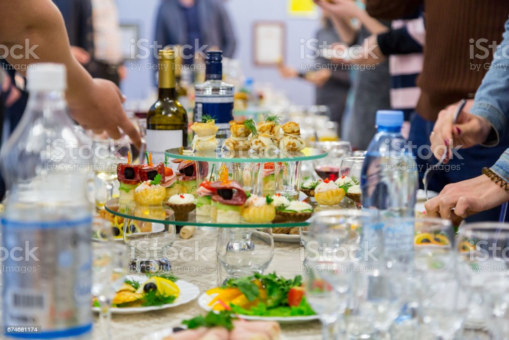 Employees of the company at the Banquet. Table with delicacies, alcohol and snacks. A gala reception. Catering stock photo