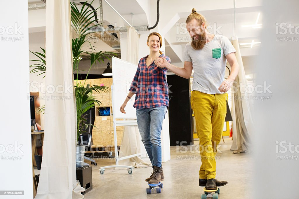 Employees skating through the office stock photo