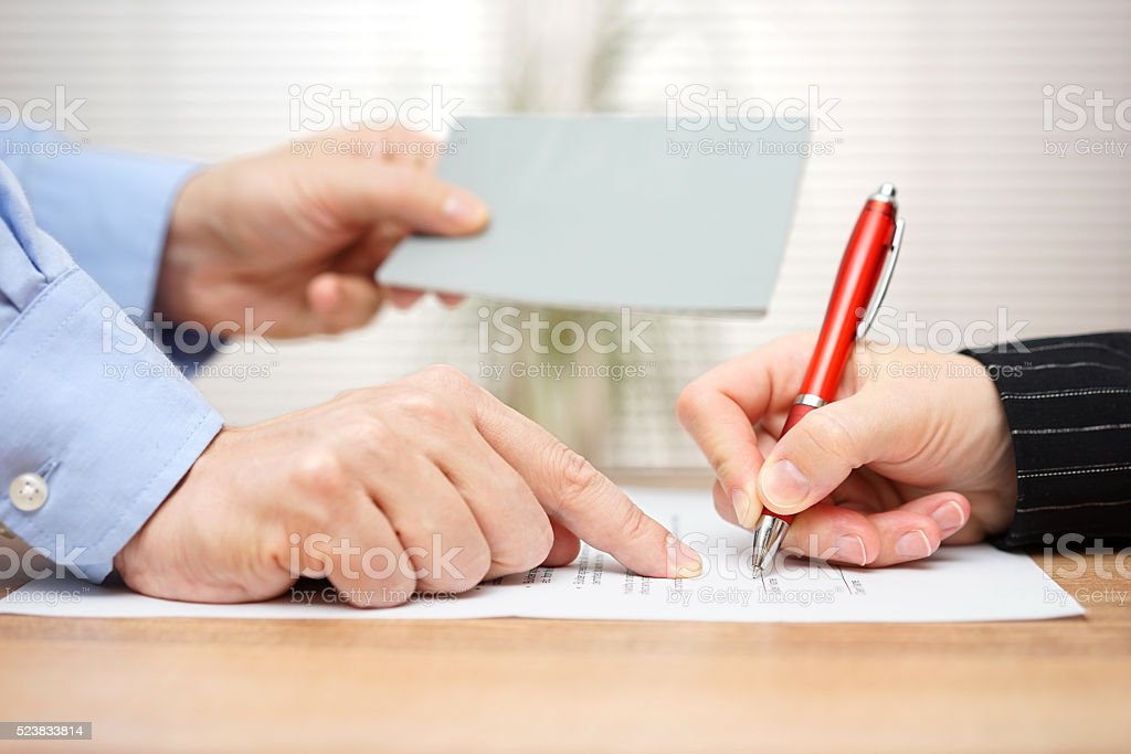 employer shows employee where to sign and giving her booklet stock photo