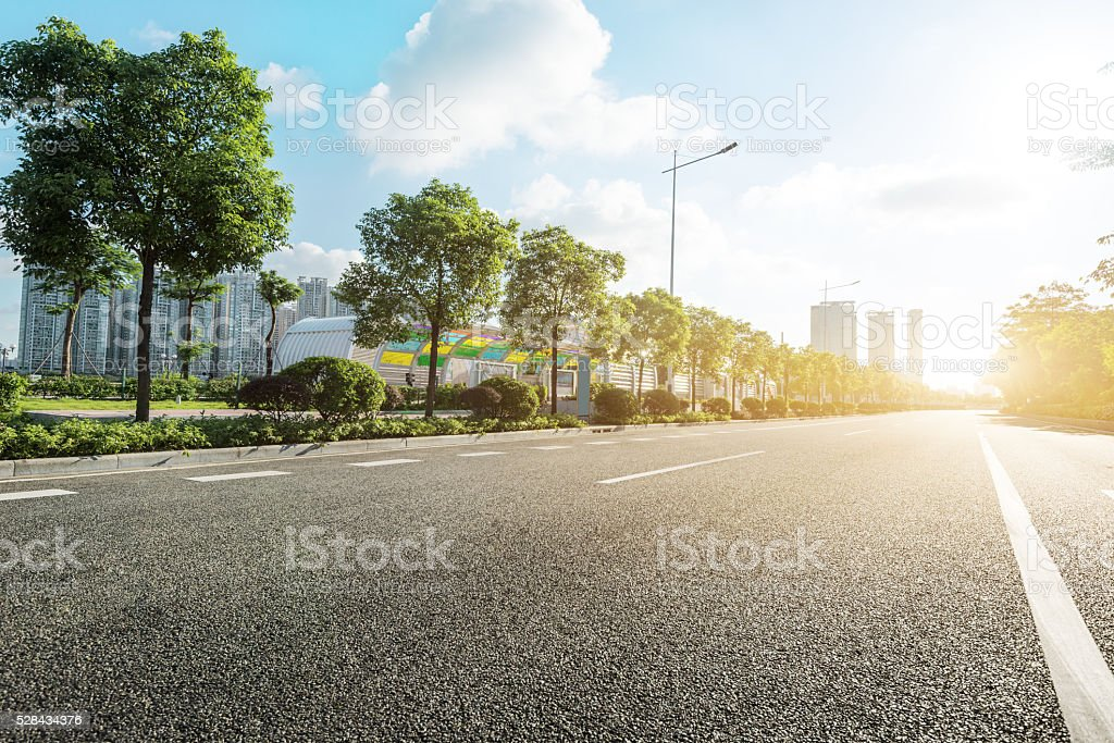 empty asphalt road in modern city at sunrise stock photo