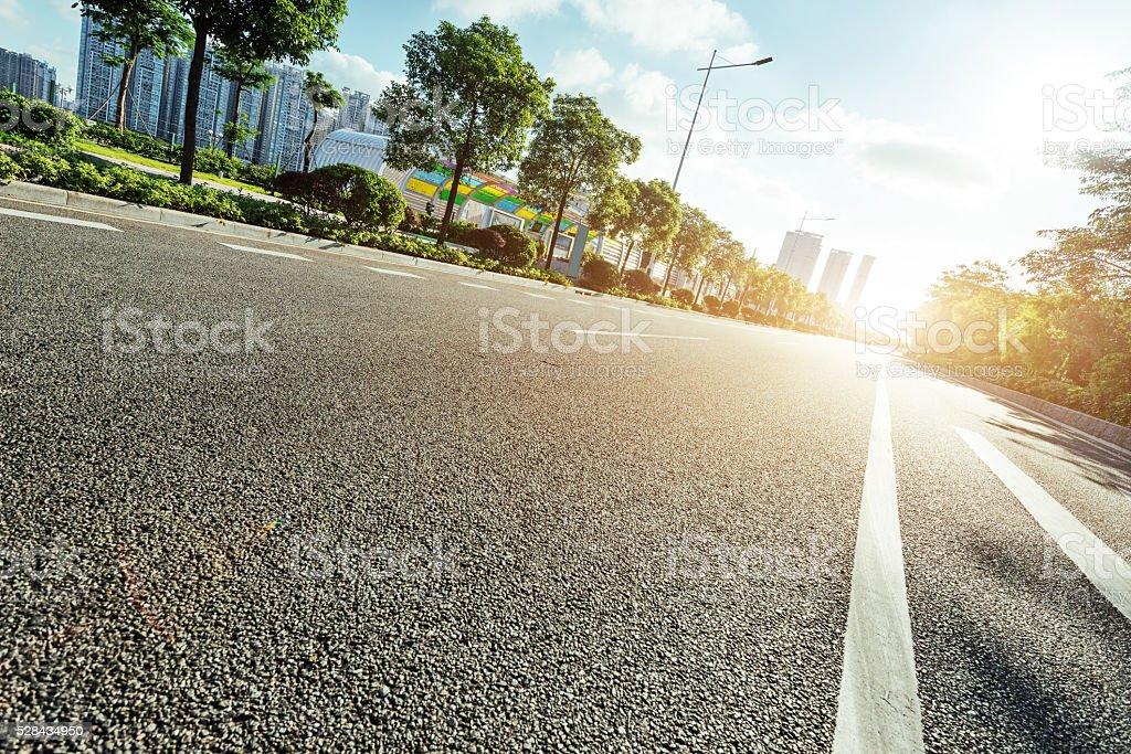 empty asphalt road in modern city at sunrise stock photo