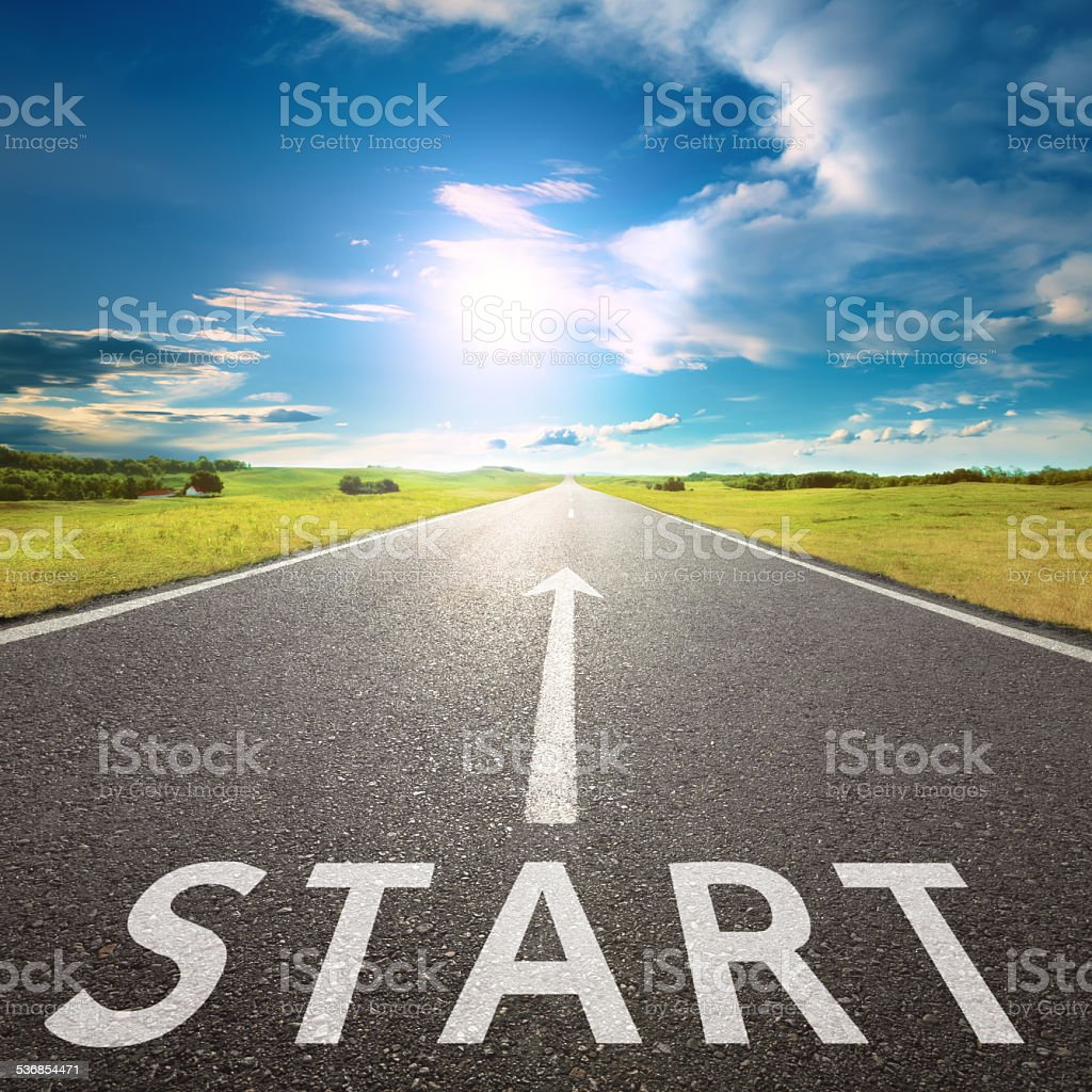 Empty asphalt road with a sign start against sun stock photo