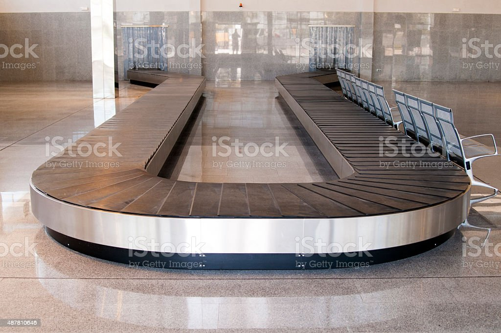 empty baggage carousel in airport hall with granite floor stock photo