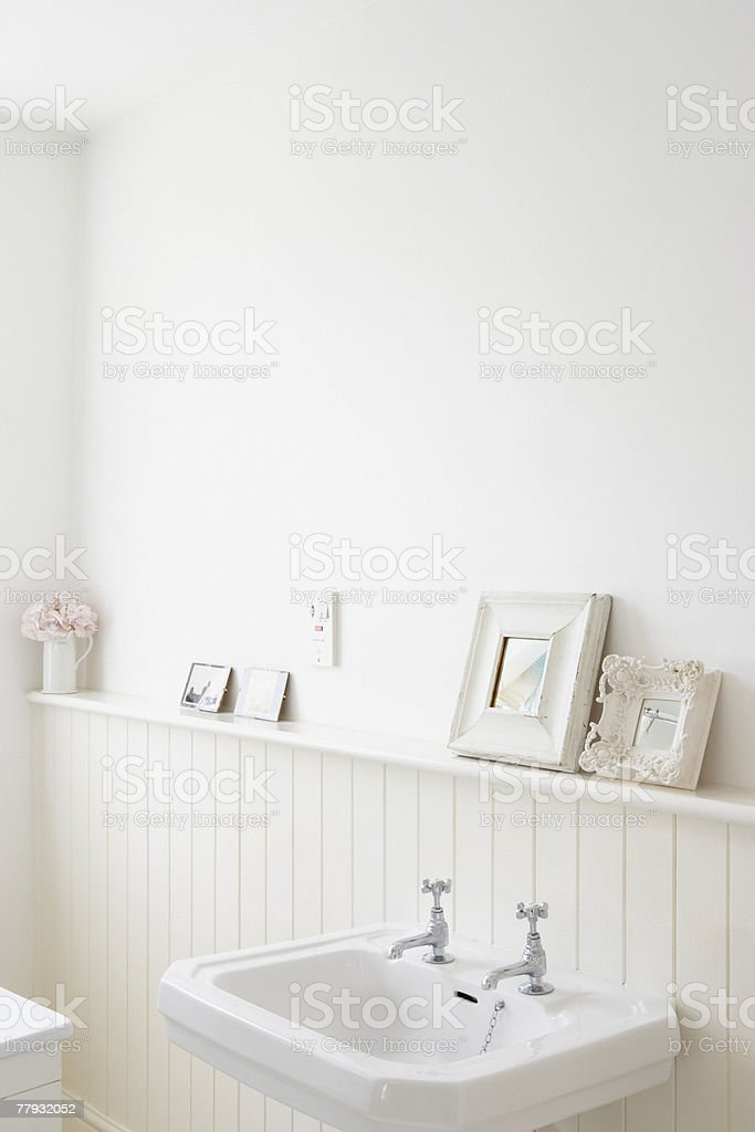 Empty bathroom with pictures on shelf stock photo