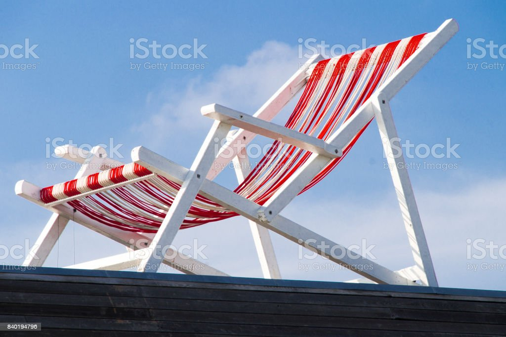 empty beach chair, red white stripes, against blue sky stock photo