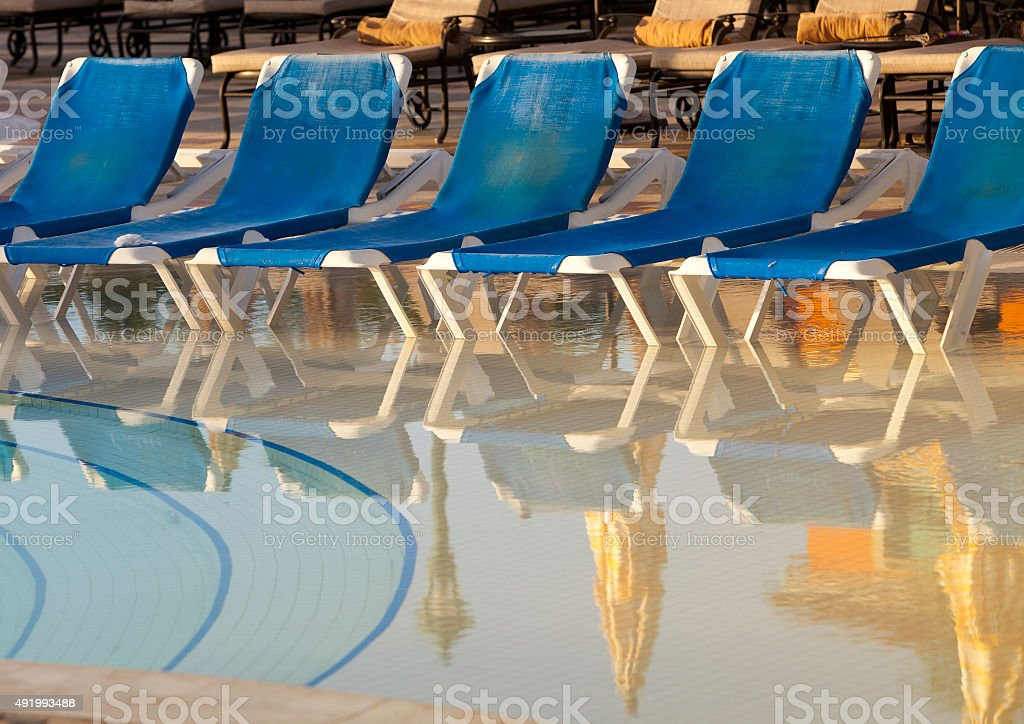 Empty beach chairs near  pool stock photo