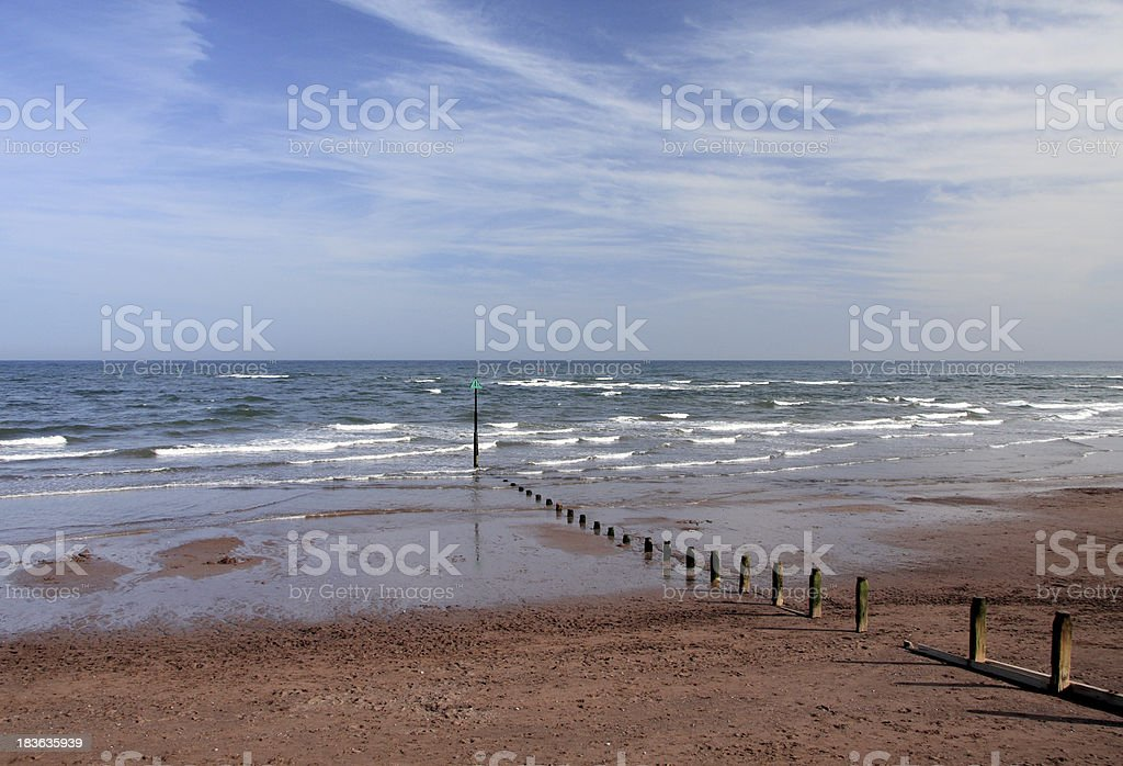 Empty beach under blue sky at British seaside - horizontal royalty-free stock photo