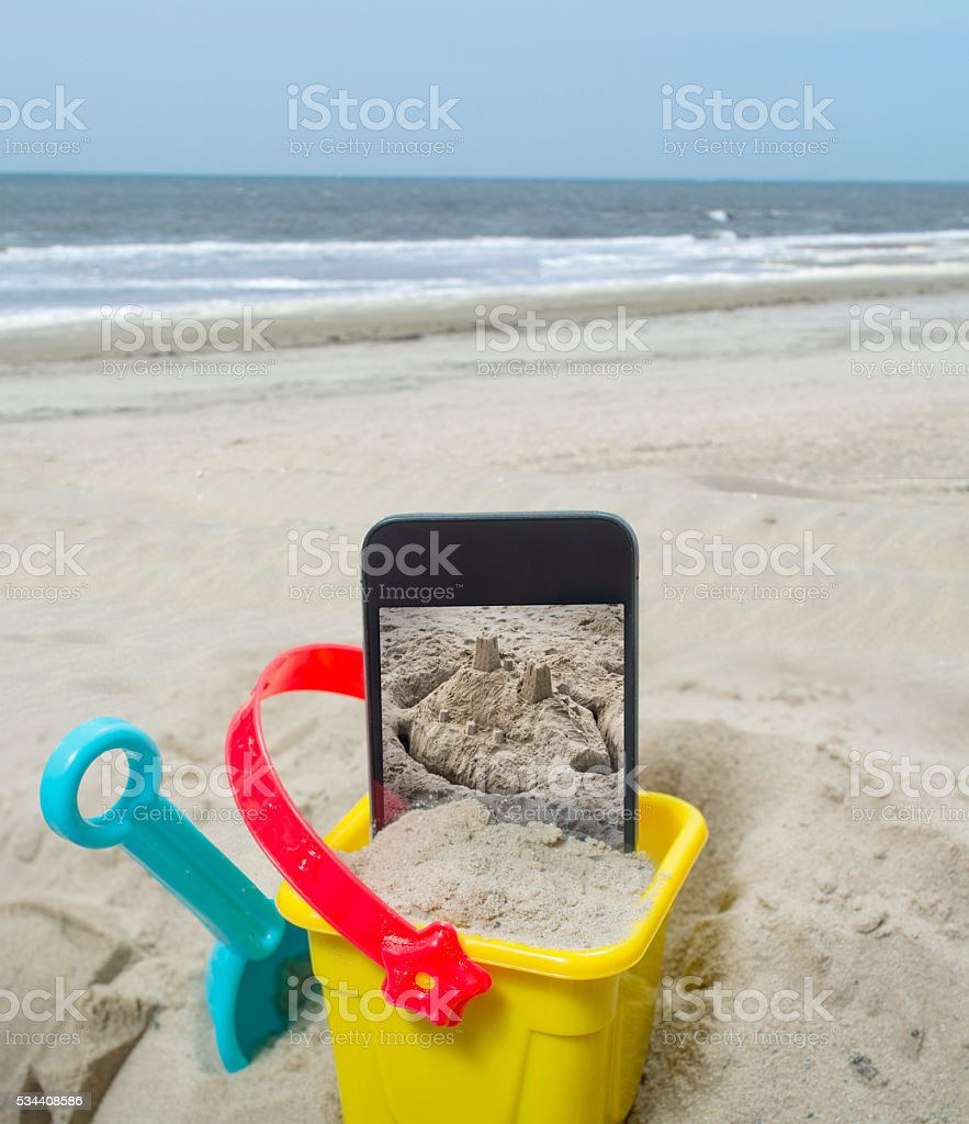 Empty beach with sand castle on smartphone with clipping path stock photo