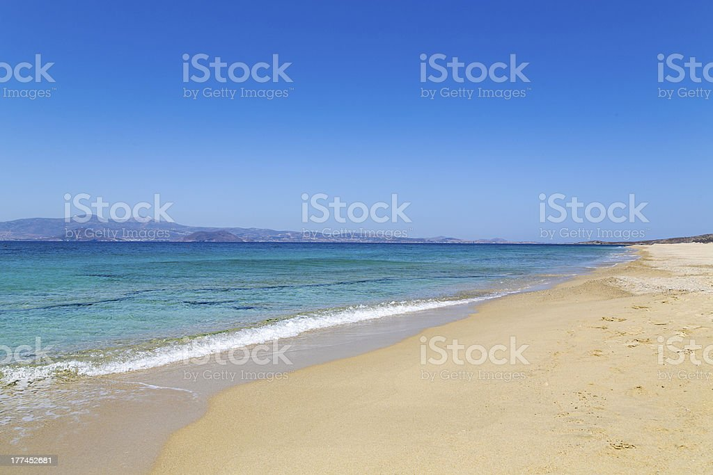 empty beach with turquoise ocean and an island in background stock photo