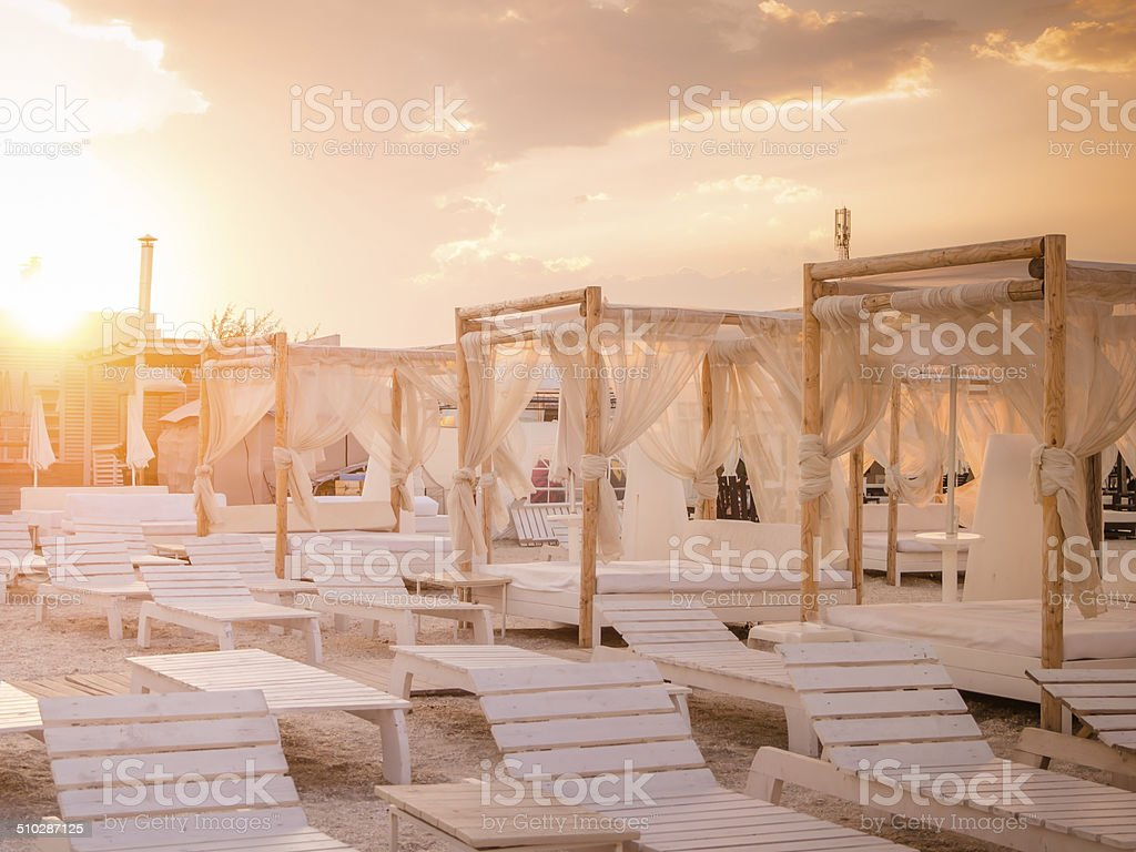Empty beach with white lounge chairs and baldaquins. stock photo