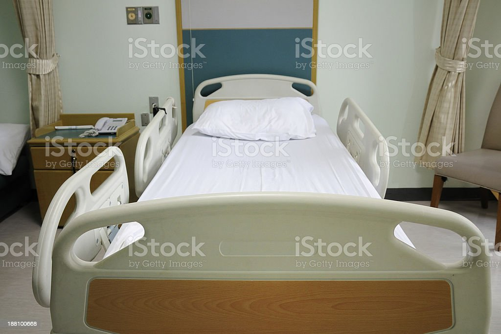 Empty bed in hospital room stock photo
