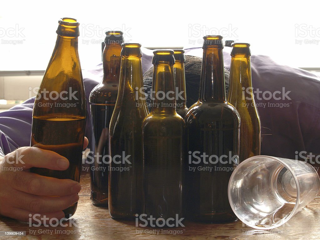 Empty beer bottles and a drunken man next to them royalty-free stock photo