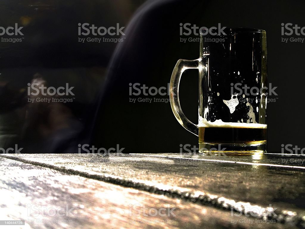 Empty beer mug sitting on wooden bar stock photo