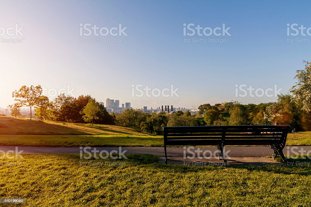 Empty bench in Greenwich Park at sunset stock photo