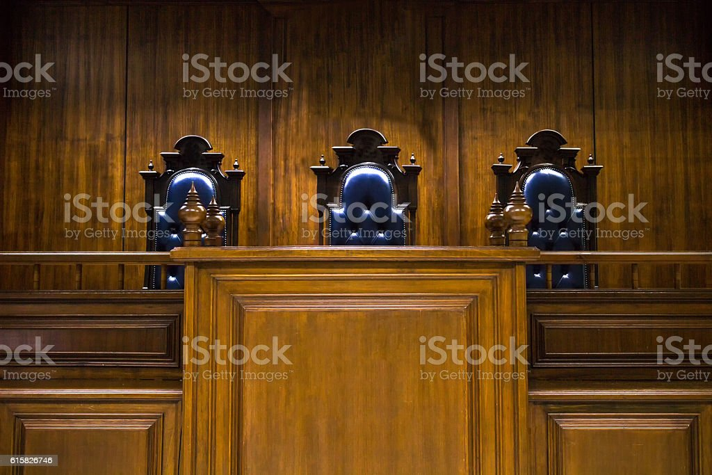 Empty bench with judge chairs in courtroom stock photo