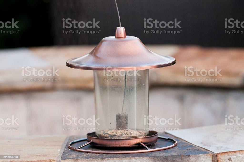 Empty bird feeder sitting on flagstone stock photo