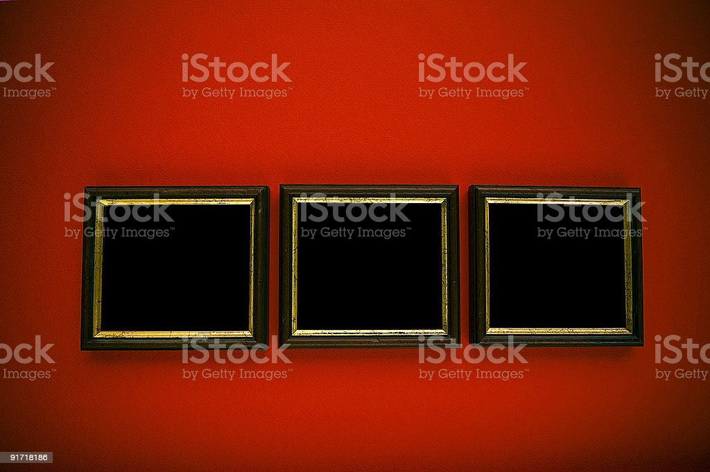 empty black and gold frames on red wall stock photo