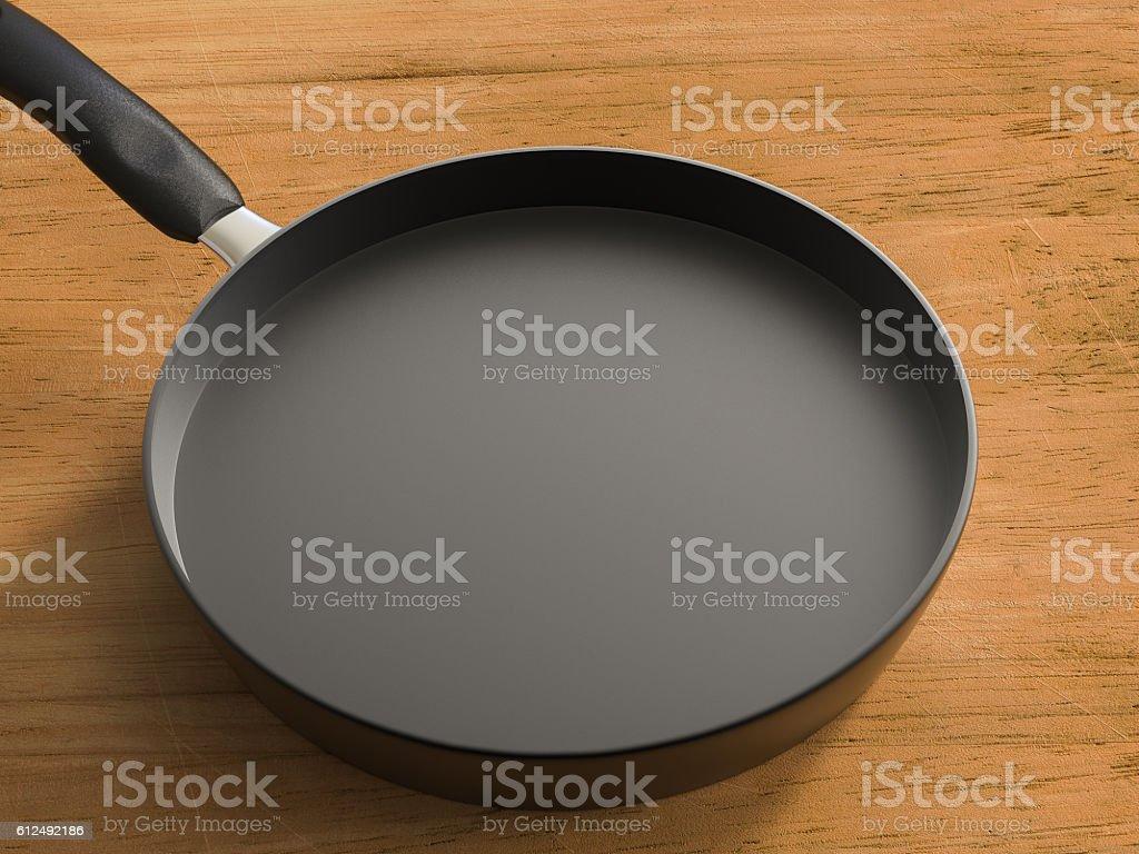 empty black pan on wooden table stock photo