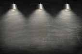 Empty blackboard lit from above by 3 suspended lamps.
