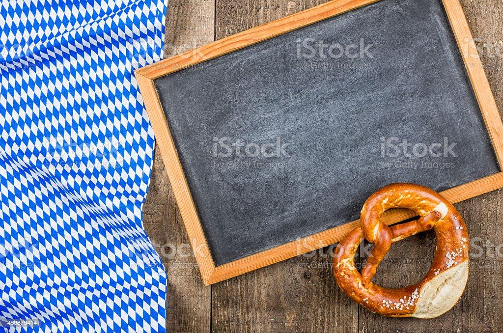 Empty blackboardand a pretzel with a bavarian diamond pattern stock photo