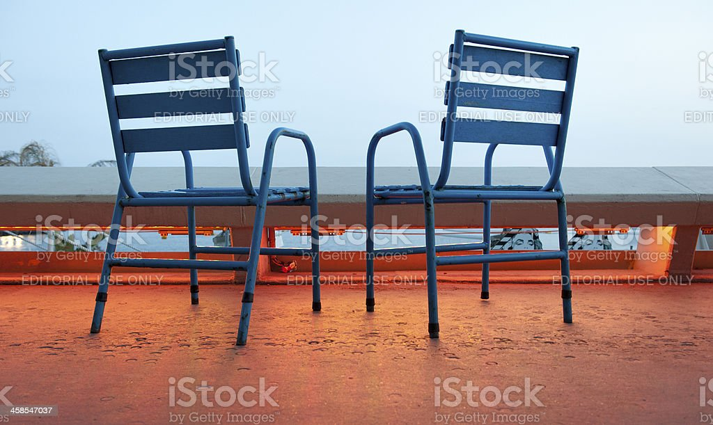 empty blue chairs on boulevard at sunset in Cannes France stock photo