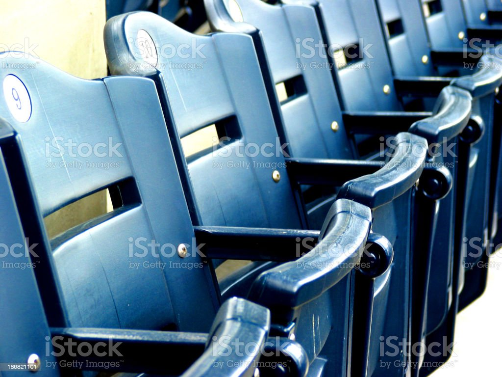 Empty blue plastic seats folded up in a stadium royalty-free stock photo