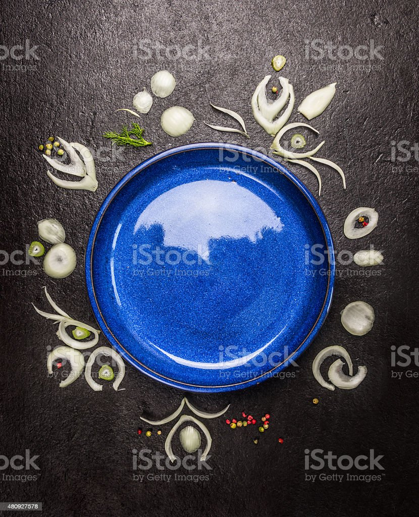 Empty blue plate with onion patter non dark stone background stock photo