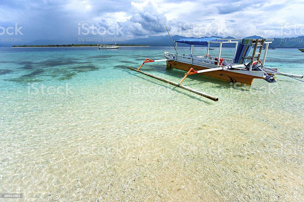 Empty boat in shallow sea waters of Gili Meno, Indonesia stock photo