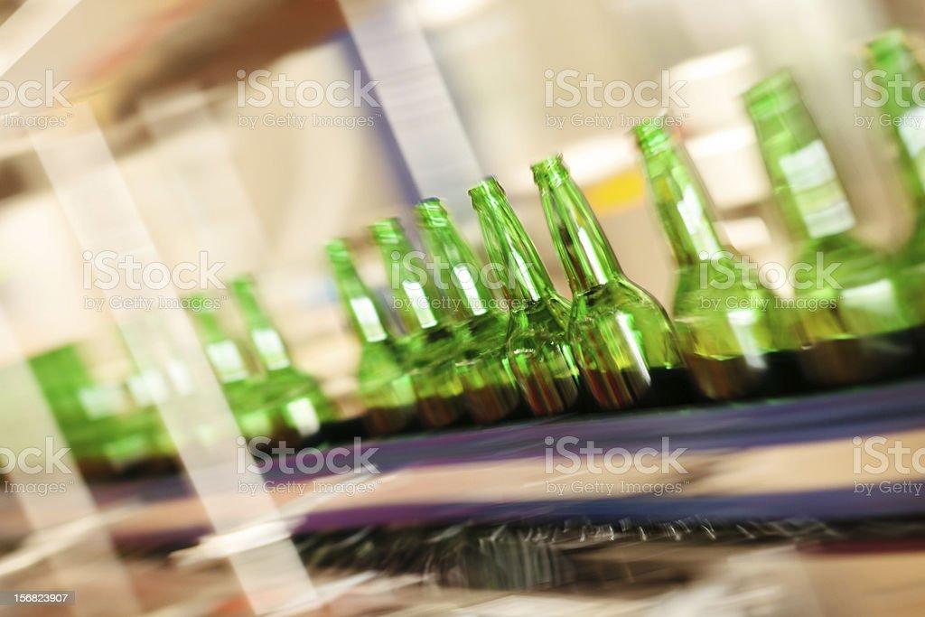 Empty bottles on factory conveyor belt (long exposure) stock photo