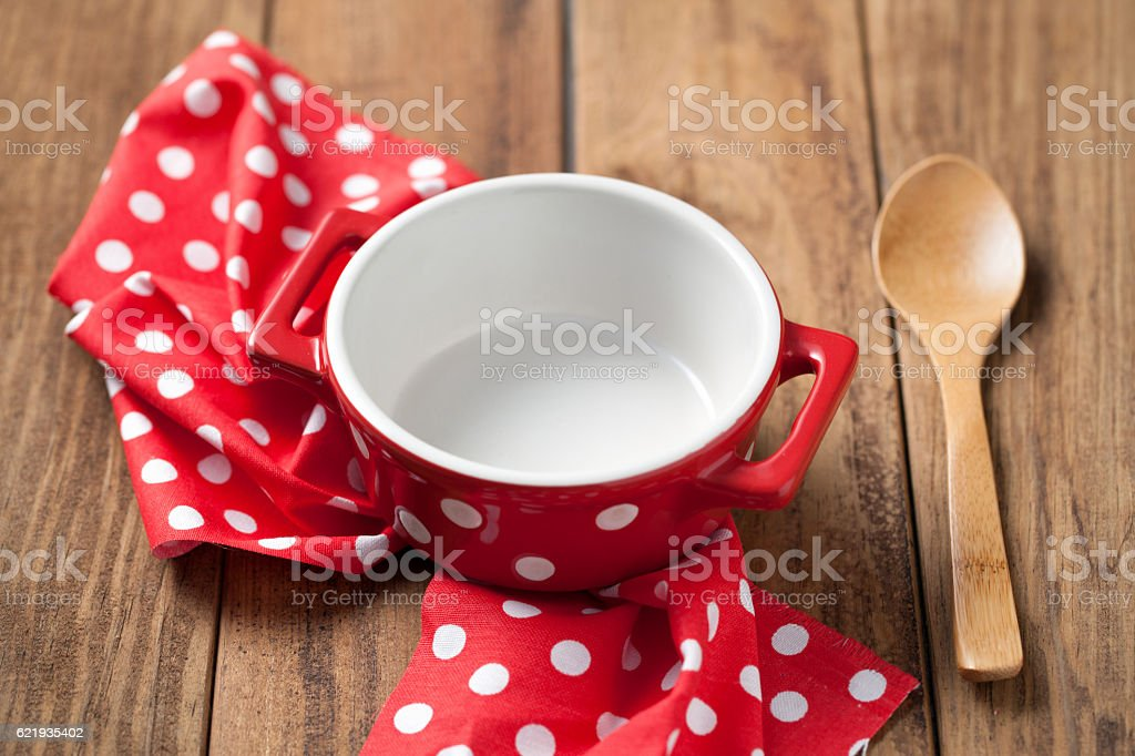 Empty bowl and spoon with napkin on wooden table stock photo