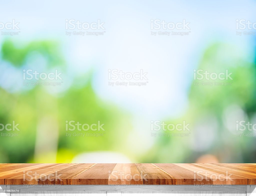 Empty brown wood table top with sun and blur tree stock photo