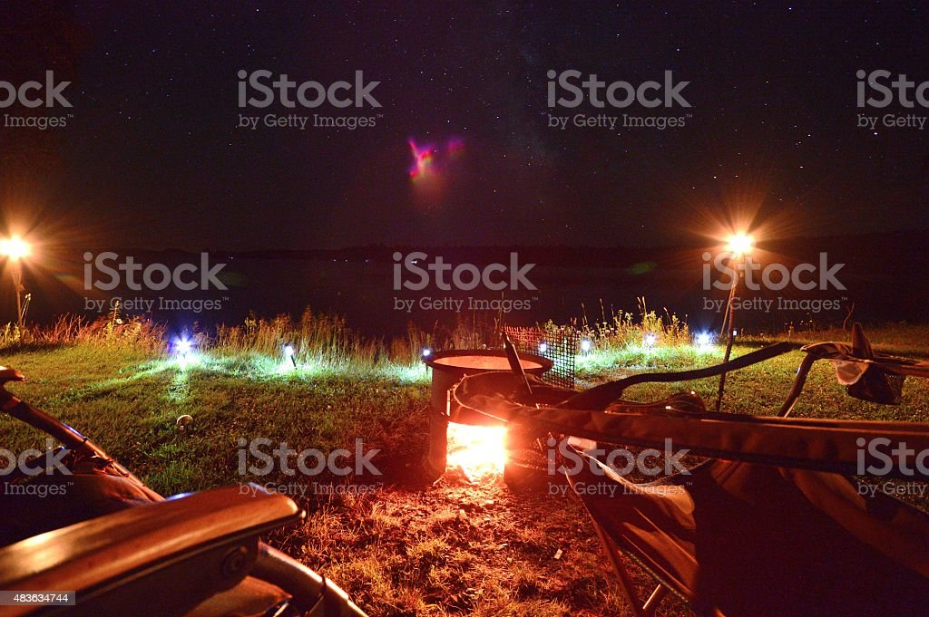 Empty Camp Chairs With Lit Fire and Starry Sky stock photo