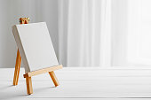 Empty canvas on easel on white desk.