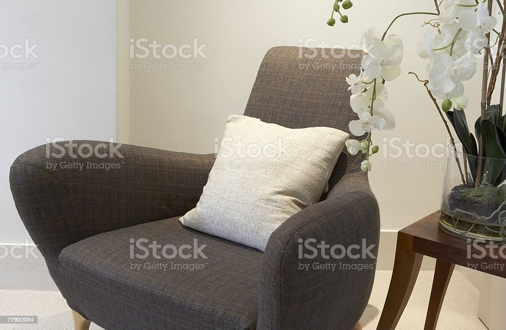 Empty chair and end table with an orchid on it royalty-free stock photo