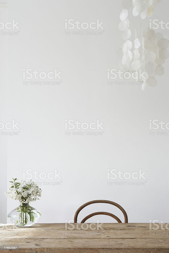 Empty chair and vase on table stock photo