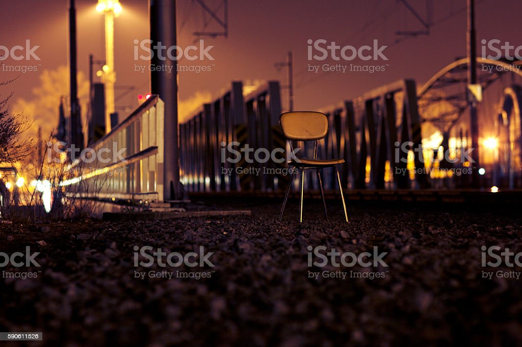 Empty Chair in Front of a Railway Bridge stock photo