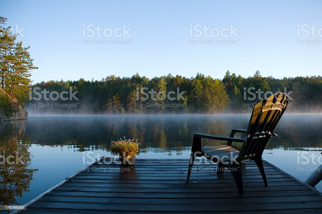 Empty chair overlooking a lake with mist and a forest stock photo