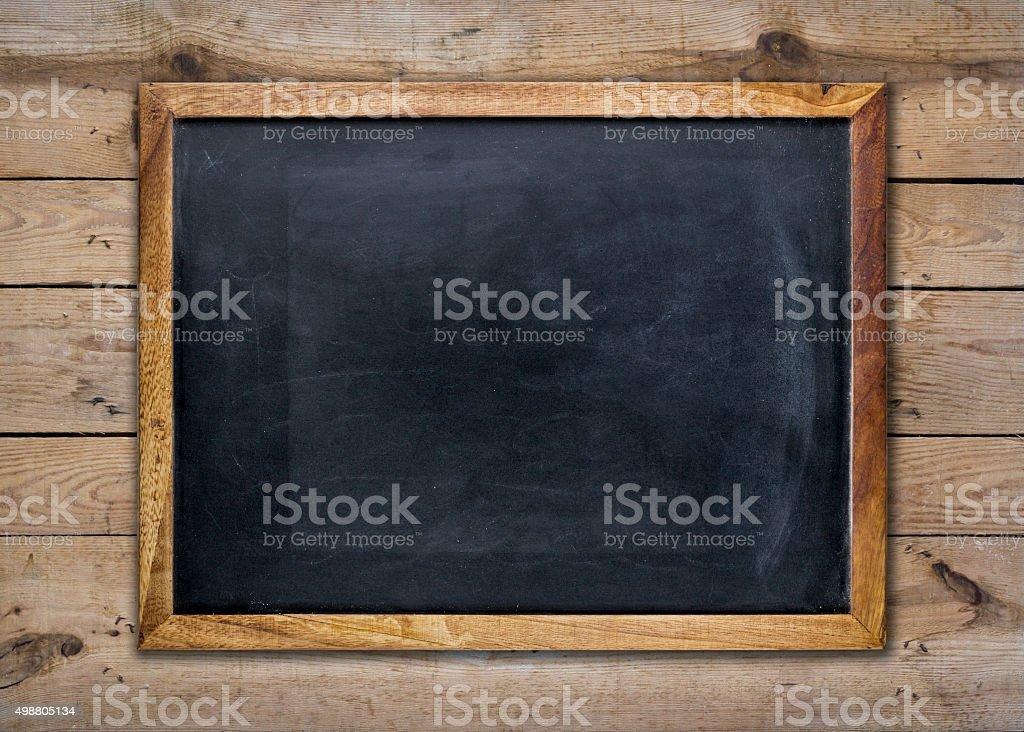 Empty chalkboard on wooden surface stock photo