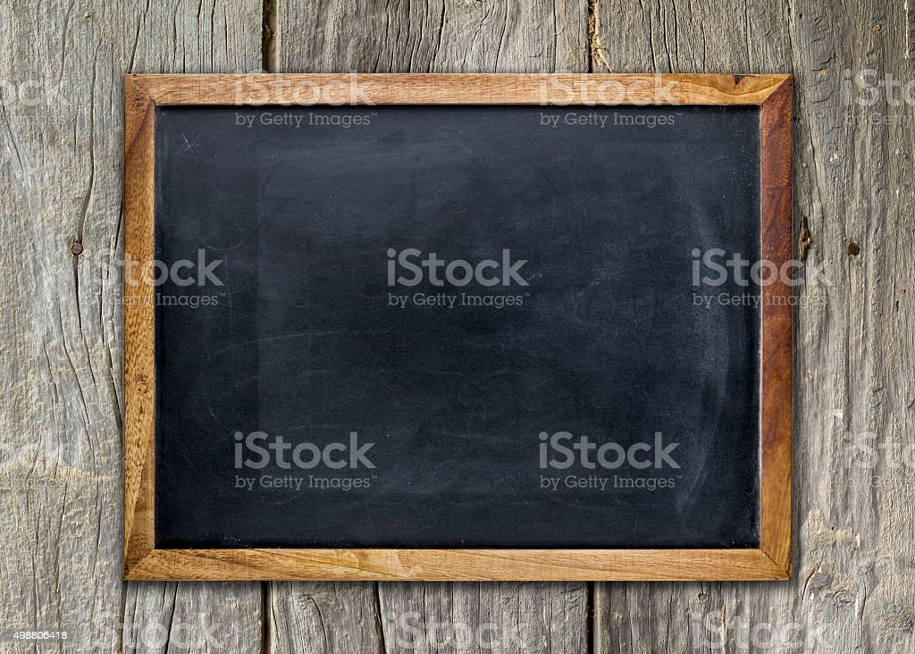 Empty chalkboard on wooden surface stock photo