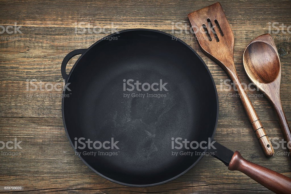 Empty Clean Cast Iron Frying Pan On Wooden Background stock photo