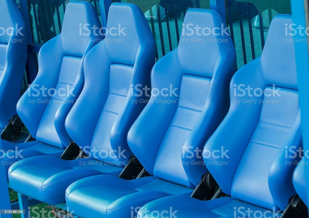 Empty coach and reserves blue bench on a football stadium stock photo