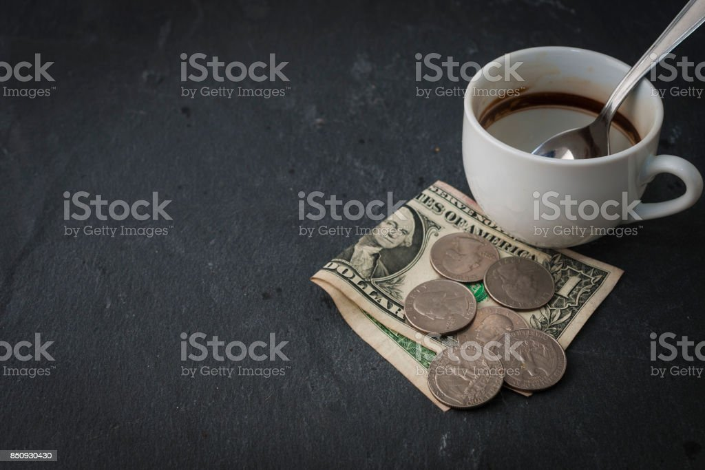 Empty coffee cup with cash for payment and tips stock photo