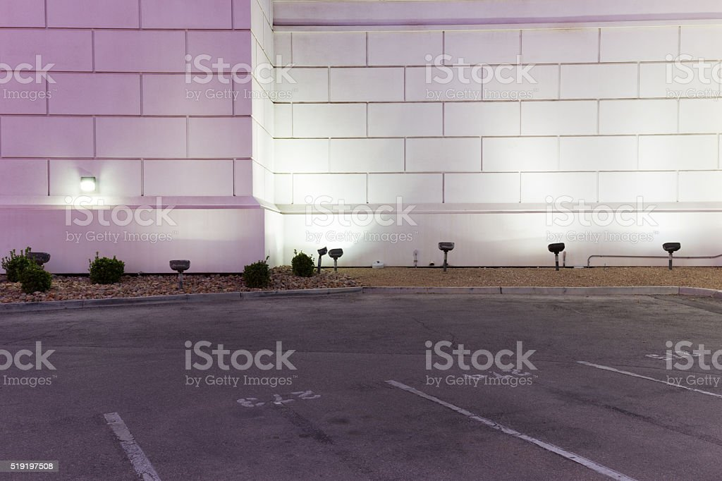 empty concrete parking lot and brick wall at night stock photo